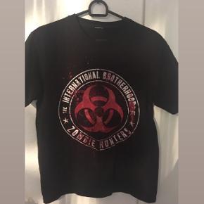 """🧟♂️🧟♀️ Så cool sort t-shirt med print/merchandise t-shirt med zombie design og quote: """"The international brotherhood of zombie hunters"""" (så er du totally ready til når en zombie apocalypse lige pludselig er i udbrud! 😂😎), købt på nettet, størrelsen har jeg klippet ud men mener det er en str M/38, unisex design. 💥  Kan passes af flere forskellige størrelser, alt afhængig af hvordan  man gerne vil have den skal sidde.  Sælges da den desværre er for stor til mig. 😩 Aldrig brugt.  Købt til omkring 250-280 kr.  Hvis den skal sendes, betaler køber fragt.  Mvh Betina Thy"""