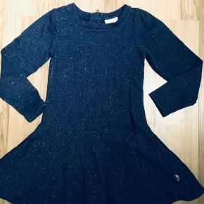 Festlig kjole i mørkeblå med guldglimmer. Fine detaljer med lidt puf-ærmer og strut. Lynlås i ryggen.