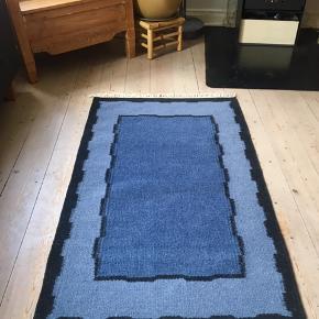 Flot tæppe i blå nuancer og sort. Det måler 90x160cm uden frynser.