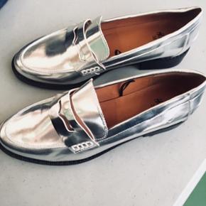 H&M sølv loafers. Helt nye.  Str 38  Ønsker køberen at få tilsendt, betales fragt naturligvis af køberen.  Afhentning på Frederiksberg. Ønsker ikke at bytte😊