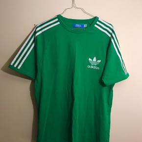 Super fed grøn adidas t-shirt med striber henover skuldrene. Ærmet er raglan stil og meget sporty, men ikke en decideret sportst-shirt