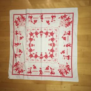 Lille juledug i rødt og hvidt med de sødeste nissemotiver. Måler 83x86 cm Pris kr 30