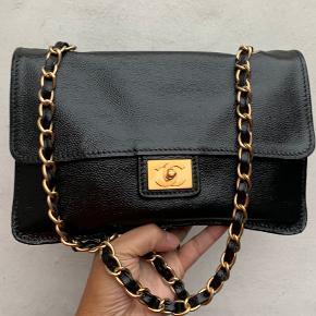 """Vintage chanel skulder taske i blød caviar.  Tasken er fra 2002-2003 og er en sæson taske. CC-logoet er forgyldt med 24 k guld.  Tasken er blevet malet, den var hvid før, det er derfor, de er en hvid plet inde læi tasken på klappen, så man kan se chanel stemplet i guld er forholdsvist synlig (det er lidt slidt af men kan skimmes).   Der er ingen mangler eller skader på tasken uden på, men den er plettet inden i.  Tasken er 26-17-6,5 og kæden er 45 lang.  Tasken sælges med kasse og dustbag.   På nogle af billederne har jeg den på crossbody på sidste billede, jeg er bred over skuldrene, så den sidder højt på mig.  Tasken er autensiteret af """"etinclair autensitations"""" og af Vestiere Collective.  Sælges med Kassen, dustbag og autensitetspapier både fra VC og EA.  Jeg sender gerne flere billeder. Prisen er fast."""