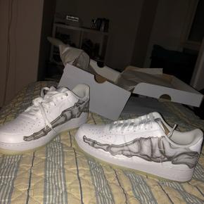 """Sælger disse fede Nike Air Force 1 """"Skeleton"""" Skoen er udsolgt alle steder og er en limited model, som blev lanceret i forbindelse med halloween     Str 45  KØB NU FOR 1050kr!    Cond 10/10 kun taget ud af æske for at få taget billeder.  Har kvit.     Kan lave meetup i Kbh og omregn"""