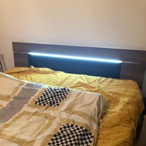 Doppelbett aus Holz ohne Matratze mit Licht.