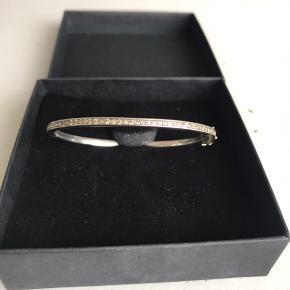 Smukt og cool lille sølvarmbånd / bangle fra Sys Bjarnhof med brune diamanter hele vejen rundt og lås i 18 karat guld. Har oprindeligt været mørkt rhodineret, men synes det er smukt, som det er nu. Ellers kan man evt rhodinere det igen. Nypris 9500 Venligst se mine andre annoncer!