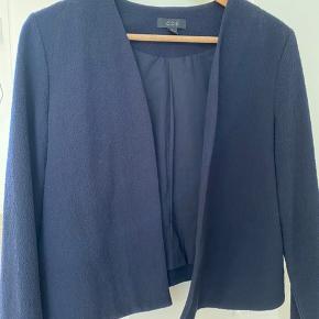 Smuk dyb mørkeblå ( svært at gengive på foto) Jakke i enkelt design uden knapper el andet. Har en lidt ruflet struktur på overfladen og er et blandings produkt med uld. Virkelig fin 💙