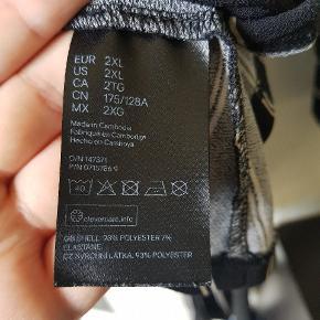 Flot slå-om bluse fra H&M+ i str 2XL. Sort med striber i hvid og beige. Der er medfølgende bindebånd i taljen, som kan fjernes.  Har været brugt, men er i god stand.