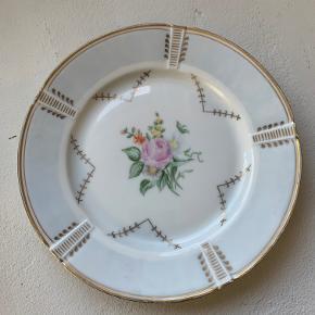 Bing og Grøndahl mindre tallerken/fad. Romantisk med blomstermotiv - guldudsmykning og svag lyseblå fane . Ingen skår eller revner. Mærkaten bagpå indikerer at den er fra 1950'erne Diameter 20 cm. Pris kr 75.