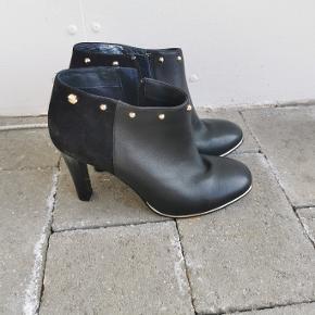 Varetype: Lækre støvletter (skostøvler) i læder/skind og ruskind. De er højhælede og med guldnitter rundt i kanten øverst. Ankelstøvler der er brugt ganske lidt. Der er lidt mærker på de højhælede sko. Der er lynlås på indersiden og i kanten rundt nederst er der guld.   Brand: Tommy Hilfiger   Størrelse: 37, uk 4, usa 6½, cm 23½ Farve: sort med guldnitter og blå såler Estimeret nypris: 1.900 kr  Materiale: Læder/ruskind Vægt: 555 g  Style:  D1285ENISE 8C FW56821351 GRE-GRE 09/15  Mål Hæl: 9,5 Indvendig hæl: 7,3  Klik på Køb nu knappen og køb med det samme. Hvis der er mere på min profil du ønsker at købe med, tilføjer du blot det.  Mine annoncer er delt op i kategorier, dvs. alle jeans, jakker, kjoler etc. er samlet hver for sig på profilen. Scrol og se alle ting i shoppen.