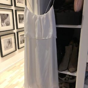 Fin hvid satinkjole med spagetti stropper, som krydses på ryggen. Perfekt til konfirmation eller dimension