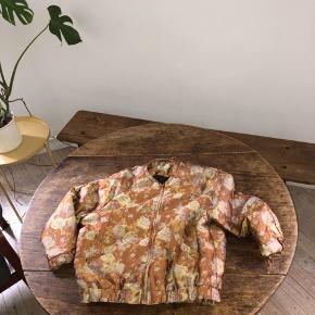 Sød bomber agtig overgangs jakke, i brun rust shiny tekstil med blomster mønster i gul og lyserøde nuancer. Den er let vatteret og er perfekt i efteråret og vinter med en god strik eller hættetrøje under. Jakken har lidt tråde der stikker ud, de kan evt klippes af. Jeg har aldrig rigtigt lagt mærke til dem før jeg satte den til salg 💁🏻♀️