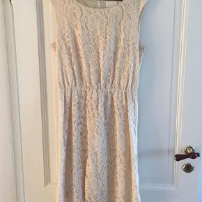 Varetype: Midi Farve: Nude Oprindelig købspris: 900 kr.  Smuk blondekjole i den fineste farve. Kjolen er med for og elastik i taljen. Brugt få gange.