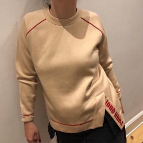 """Lækker blød sweatshirt - beige med røde kanter og broderet """"Pour Quoi"""" i slidse i højre side - har aldrig været brugt"""