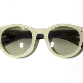 En flot solbriller der er født af et samarbejde mellem Garrett Leight og Amelie Pichard. Model Pamela 48 - 23. De har meget overfladisk brugsspor, der kan medgives et ikke originalt etui hvis det ønskes.