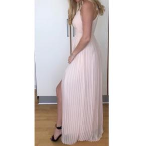 Super fin galla kjole med fin detalje omkring brystet, og en slis til benet. Kjolen har været brugt én gang i ganske få timer til et bryllup, fremstår derfor som ny.  Nyprisen er 626 kr. Kjolen er udsolgt på deres side.