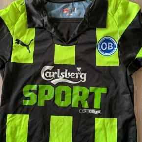 Ob Fodboldtrøje str. 152/xs. Med Carlsberg reklame foran på blusen. Blusen har lidt slidt på syning bag på få steder, men stadig brugbar og fremstår meget pæn.