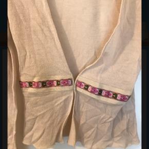 Den yndigste lille pudderfarvet cardigan, den er ca 50 cm lang og er i 100 % Virgin uld