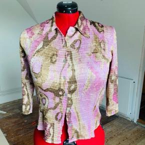 Meget velholdt og virkelig lækker Gerry Weber skjorte i crinkled stof med masser af stretch. Enkelte palietter hist og her på forside.  Flot til et par jeans.  God fast pris.   Tænker det er en str 40.  Lilla/rosa og armygrønne farver.