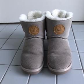 Lækre varme ruskinds støvler med lammeuld og små sløjfer bagpå. De fejler ikke noget, men forret er lidt fladt under foden. Uld bliver hurtigt trådt fladt. Den ene sål er slidt lidt ved hælen bagerst se sidste billede.  Svarer til str. 37