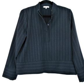 Flot højhalset bluse med skjult knappelukning ved halsen.  En flot klassisk bluse der har været brugt to gange. Længde: 55 cm Brystvidde: 104 cm Består af:95 % polyester, 2 % elastine og 2 %viscose. Sendes med DAO.