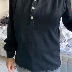 Sort skjorte med stolpelukning og pufærmer. Farven er helt sort.