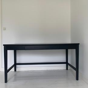 Lækkert sort gedigent skrivebord fra Et Hjem/ Sanders i træ. Står i rigtig  pæn stand. Nypris ca. 5500,-!  Bredde 150cm Dybde 75cm Højde 75cm