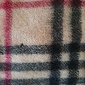 Ægte Burberry tørklæde i 100% cashmere i de originale farver. Måler ca 30cm x 155cm (inkl frynser). Kvittering haves desværre ikke længere da jeg købte det for ca 15 år siden 😅  Det har desværre fået et lille hul og et lille område med slid (se billeder), men kan sagtens stadig bruges.