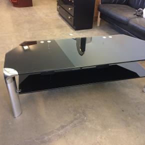 Sofabord, glas, b: 130 l: 50 h: 44  Kan leveres! Fint glassofabord med to glasplader. Rigtig flot men har et par defekter på den ene stolpe, der holdes sammen af tape. Står rigtig fint dog (183.03)  Fuld returret tilbydes i tilfælde af skjulte fejl/mangler!