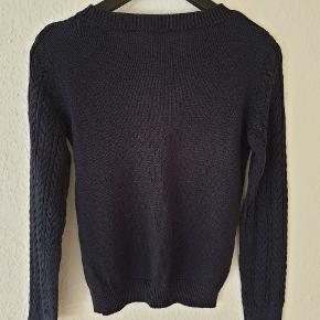 Kabelstrikket trøje fra H&M i mørkeblå, ribkant i halsudskæring, ved ærmer og forneden.  Den er hverken falmet på mave eller ryg, som det ligner på billederne - beklager det dårlige lys.  Køber betaler forsendelsen.