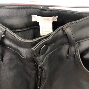 Fede skinnende bukser i noget satin-agtigt stof, men bukserne er tætsiddende og lidt ligesom denimbukser - blot med det glatte/bløde stof. Der er et enkelt sted, hvor trådene er gået lidt op (se billede), ellers fejler de ikke noget.