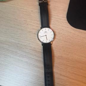 Ur med sort læderrem og sølv urskive fra Daniel Wellington sælges. Det er brugt en del, men fungerer som det skal :-) urskiven er 36 mm. Mangler nyt batteri