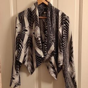 Lækker kort jakke/cardigan i sort og hvidt mønster. Fin kravedetalje og den går ned i spidser foran.