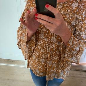 Skøn bluse fra Second Female i en smuk ørkenbrun farve og med print af blomster. Mindy Blouse har rund hals og fine flæsedetaljer. Der medfølger aftagelig ørkenbrun top.  100% Viscose Top: 100% viskose skånevaskes ved 30 grader  Brugt 2 gange og fejler intet.