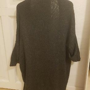 Oversize sweater/cardigan i strik. Knap til at lukke foran.