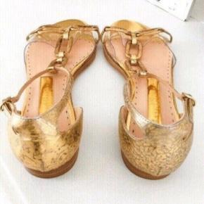 Smukke eksklusive designersko fra Rupert Sanderson, købt i Kassandra i København, Nypris var omkring 4500 kr. Guldfarvet, flats, sandaler, str. 38,5.  Sandalen måler 25,5 cm.   Kun lige brugt 1 gang, Næsten som NYE.