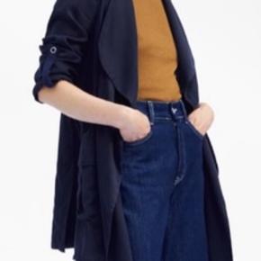 """Fed, """"flowy"""" marineblå jakke med krave og lange ærmer, der har en indvendig løkke og knapdetalje. Justerbar indvendig løbebånd. Frontlommer. Superflot, asymmetrisk fald. 100% Lyocell. Aldrig brugt, prismrk. stadig på. Billede 1-3 fra hjemmesiden. Det sidste billede er mit."""