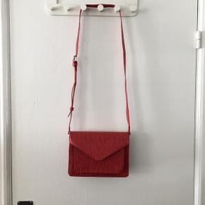 Rød Ganni-inspireret cross-over taske i krokodille-look, med justerbar rem og mange rum 🌺 Aldrig brugt og fremstår derfor som ny. Kan afhentes i Aarhus C eller sendes mod betaling af porto 📦📮