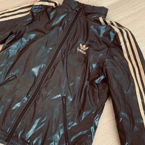 Adidas vind-jakke/trøje med guld striber.  Kan både bruge af kvinder/mænd  Er krøllet, efter at have ligget i skabet, men en vask gør den fin igen :)
