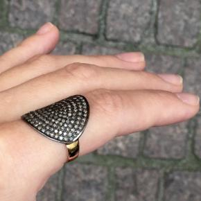 SUPER ELLIPSE, Fold Over Ring, 2-tone  Dark Silver/14K Gold/Diamonds  Large amazing ring, that folds over your finger, showing off more than two carat of grey diamonds. The cool dark silver set against beautiful soft gold is giving this ring a very modern and updated expression.  Dimensions	30x24mm, frame 3-5mm Weight	5,5g Metal	14k gold 1,60g  Dark rhodium on sterling silver 925 Stone	Grey single cut diamonds, 2,09ct Finish	High polished  Nypris 7800,-