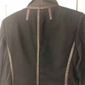 Rå skræddersyet blazer med skindbesætning fra New Yorker brandet Rag & Bone.  Blazeren lukkes med en stor hægte. Str US 4 dvarer til str 36