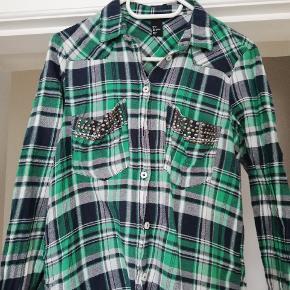 Skjorte i grønt mønster med to lommer ved bryste, som er pyntet med fine knapper. Næsten ikke brugt. Byd gerne😊