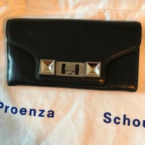 Proenza pung Virkelig god stand. Der er et kommet en lille rød streg på indersiden( se billede 3), det er ikke noget der ses :-)  Målene er: 19cm lang og 10 cm bred☺️