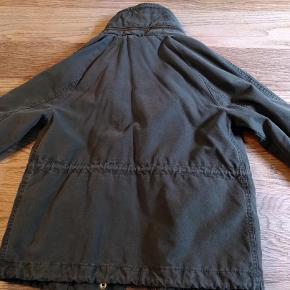 Armygrøn jakke i militærstil fra Superdry. 100 % bomuld (for i ærmer er polyester), kan vaskes. Løbegang i taljen og forneden, lukkes med kraftig metallynlås og trykknapper, to frontlommer med trykknap.