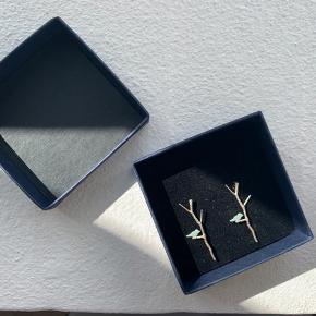 Pendulum Lovebirds Øreringe i forsølvet messing formet som grene med fugle i tyrkis. De er Nikkelfri og cirka 3 cm lange