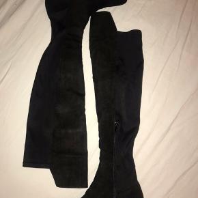 Super flotte og feminine knælange støvler i imiteret ruskind med tekstil bagpå (som er elastisk). Skaft er 50 cm bagpå, og 54 cm foran, med lille hæl på 3 cm.   Aldrig brugt, kun prøvet på et par gange, men må indse mine ben er blevet for store😅  Mærke: NLY Shoes Str. 38  BYD!!