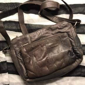 Smart lille taske i blødt skind fra Le Sac Noir. Mørkebrun, perfekt til telefon, pung og andre småting.