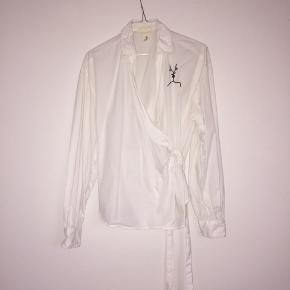 Fin hvid skjorte med wrap-effekt. Har broderet en lille illustration på brystet. God stand !