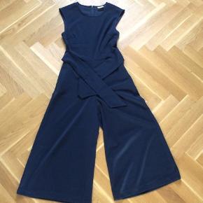 Smukkeste buksedragt med lynlås i ryggen og vidde i benene, som er korte. Størrelsessvarende. Brystvidde 44*2 cm.