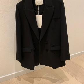 Notes Du Nord Lily Blazer Flot cool sort blazerjakke der bare er et musthave i garderoben.   75% Polyester, 20% Viscose, 5% Spandex.   Rens.